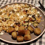 Couscous met gebakken kikkererwten, groente en falafel geserveerd